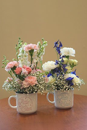 pink or blue assorted flowers in mugs to congratulate for a baby