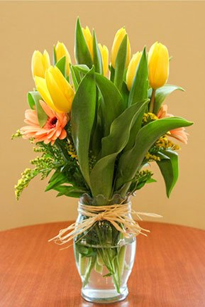 tulip and gerber daisy flower arrangement in a vase
