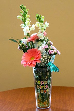 assorted flowers in a happy birthday drinking mug with a straw
